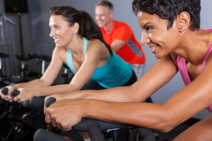 African American Woman Spinning Exercise Bike at Gym
