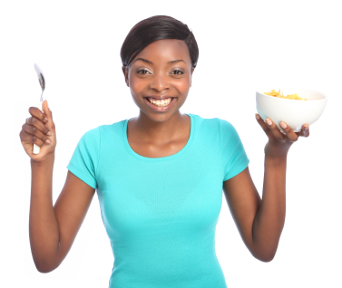 Beautiful young black woman with huge happy smile, holding breakfast cereal of cornflakes in a bowl, and a spoon in other hand. Taken against a white background.