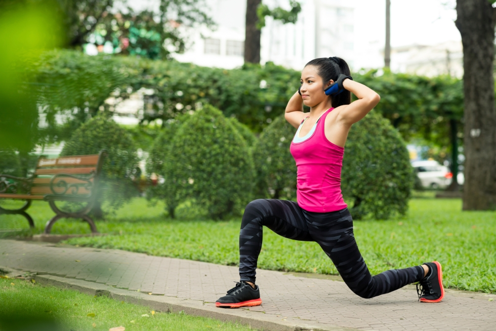 Fit Asian woman doing lunge exercise in park